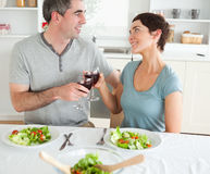 Close up of a cute couple toasting with redwine. In a dining room Royalty Free Stock Images
