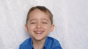 Close-up of a cute European appearance boy. Portrait of a happy child. A child laughs looking into the camera.