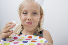 Close-up of cute girl eating birthday cake against gray background Stock Images