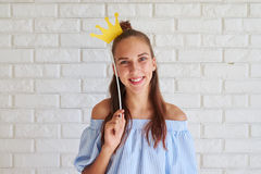 Close-up of cute girl holding paper crown over her head Royalty Free Stock Image