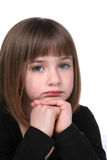Close up of cute girl's sad or thoughtful face. Close up of cute girl's thoughtful or sad face with chin on her folded hands Stock Image