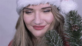 Close up of cute girl in santa claus hat with tree branches enjoying snowfall. stock footage