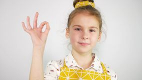 Close up cute girl showing delicious sign. Modern yellow chef uniform. Slow motion.  stock footage