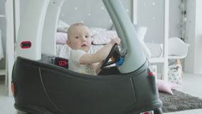 Adorable toddler girl driving toy baby car at home. Close-up of cute infant getting used to car for kids before learning to walk at home. Cute baby girl enjoying stock video