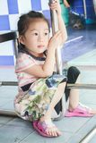 Closeup Cute little asia girl looking forward under table stock photo