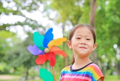 Close up cute little Asian child girl with wind turbine in the garden stock image