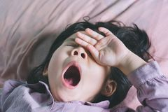 Close up Cute a little Asian girl are sleeping. A cute Asian girl yawns on the bed with tiredness from playing and a healthy boy from the rest Royalty Free Stock Photography