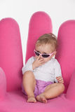 Close up of cute little baby girl looking through pink glasses. Stock Photo