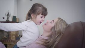 Close-up of cute little Caucasian brunette girl playing with beautiful blond mother at home. Cheerful young woman having stock video footage