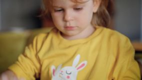 Close-up of a cute little girl draws sitting at a table with colored pencils stock video footage