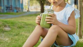 Close-up of cute little girl drinks a smoothies outdoor. Crop image of child sits on lawn and drinking fresh green smoothies stock photography