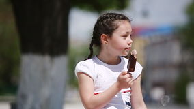 Close-up of cute little girl eating ice cream in park in sunshine summer day. stock footage