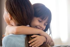 Cute little girl hug young mom showing love and care stock images