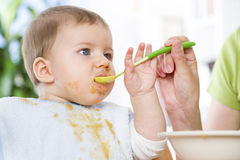 Close up of cute messy baby boy eating his meal. Royalty Free Stock Photo