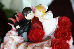 Close up of cute and playful wedding cake topper. Romantic addition to the wedding cake with bride and groom figurines, funny, cute, playful decoration for Royalty Free Stock Photos