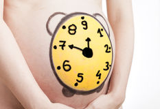 Close up of a cute pregnant belly with a clock Stock Photo