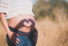 Close up of a cute pregnant belly. Shade in the form of heart. T Royalty Free Stock Images