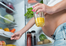 Close up of a cute pregnant belly tummy near the refrigerator Stock Images