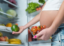Close up of a cute pregnant belly tummy near the refrigerator Royalty Free Stock Photos