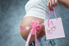 Close up of a cute pregnant belly tummy with pink ribbon. And gift present pack. Pregnant female motherhood new life concept. Side view, pregnant belly body royalty free stock image