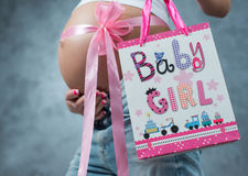 Close up of a cute pregnant belly tummy with pink ribbon. And gift present pack. Pregnant female motherhood new life concept. Side view, pregnant belly body royalty free stock photo