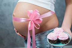 Close up of a cute pregnant belly tummy with pink ribbon. And marsh mellow. Pregnant female motherhood new life concept. Side view, pregnant belly body part royalty free stock images