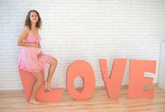 Close up of a cute pregnant woman with word love Royalty Free Stock Photo