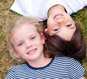 Close-up of cute siblings lying on the grass Royalty Free Stock Photo