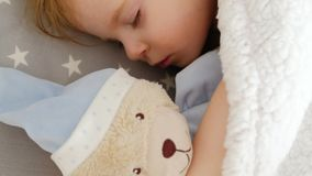 Close-up of a cute sleeping beautiful girl on a pillow with a bear stock footage
