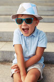 Close-up of cute small boy in sunglasses and hat with excited fa Stock Images