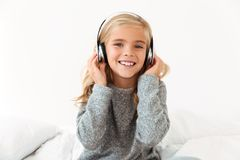 Close-up of cute smiling girl in headphones sitting in bed, look. Ing at camera Royalty Free Stock Image
