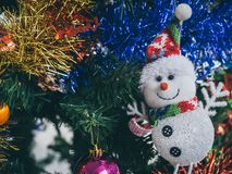 Close-up cute snowman and Christmas ornament prop decoration on Christmas tree background. Colorful Christmas background. Close-up cute snowman and Christmas stock photo