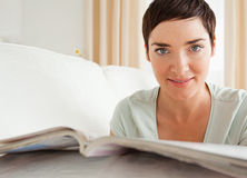 Close up of a cute woman with a magazine Stock Images