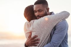 Happy young African couple embracing each other at the beach. Close up of cute young African couple hugging each other while standing together with their eyes Stock Photography