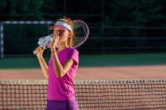 Close up cute young girl in sporty cap drinking water from plastic bottle after hard tennis training on the outdoor royalty free stock photography