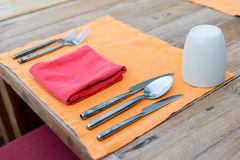 Close up of cutlery with glass and napkin on table Royalty Free Stock Images