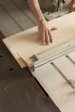 Close-up on the cutting. Hands of a worker while cutting with circular saw royalty free stock photos