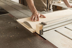 Close-up on the cutting. Young worker while cutting with circular saw royalty free stock photo