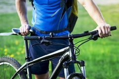 Close-up of cyclist with bicycle on background of green grass in summer. Stock Photography