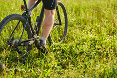 Close-up of cyclist man legs riding mountain bike on the green meadow. Stock Photo