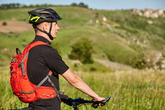 Close-up of the cyclist standing on the hill on a background with beautiful landscape. Royalty Free Stock Image