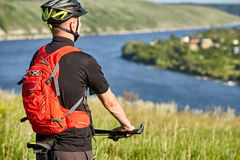 Close-up of the cyclist standing on the hill on a background with beautiful landscape. Stock Photos