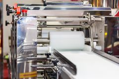 Close up cylindrical die and belt conveyor of automatic food making machine for chinese or asian food steamed stuffed buns. Production line for high technology stock photo