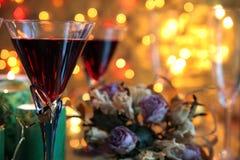 Close-up czerwone wino w szkłach, świeczce i kwiatach Fotografia Royalty Free