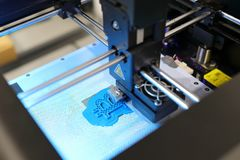 3D printer while printing blue bitcoin form. stock photography