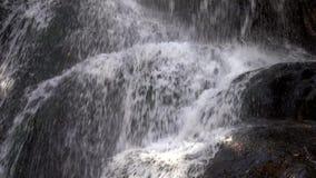 Close up da água que conecta em rochas na cachoeira filme