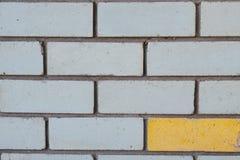 Close up da alvenaria do tijolo para o fundo Tijolos cinzentos e um amarelos Conceito Contraste fotografia de stock