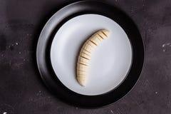 Close-up da banana cortada em uma placa em um fundo de madeira preto em uma tabela, vista superior fotos de stock royalty free