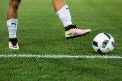 Close up da bola de futebol e pés do jogador Imagens de Stock Royalty Free