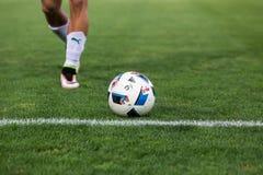 Close up da bola de futebol e pés do jogador Fotografia de Stock Royalty Free